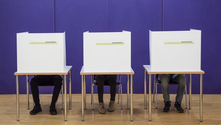 Drei Wahlkabinen mit Wählern Pressefoto Juniorwahl